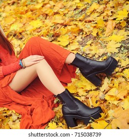 Slim woman legs with tractor sole shoes, autumn fashion concept, outdoor in autumn park