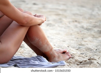 Slim woman with long legs covered with sand sunbathes sitting on a beach hugging her knees. Relax and leisure at the seaside resort