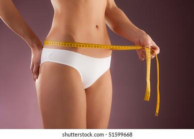 Slim woman measuring her body