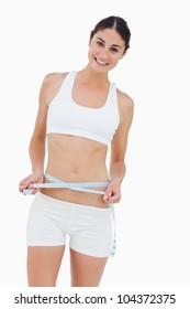 Slim woman measuring her waist against white background