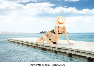 slim woman on pier and blue summer sea and island