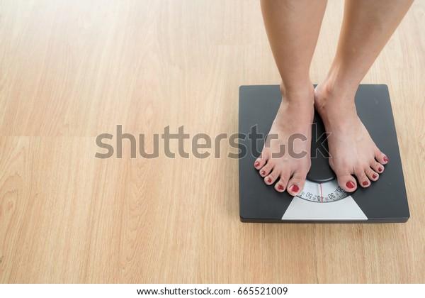 重み付けスケールのスリムな女性