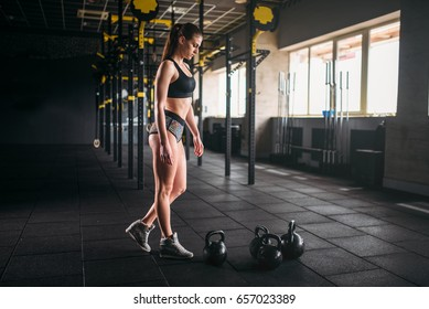 Slim woman posing with weight in fitness club