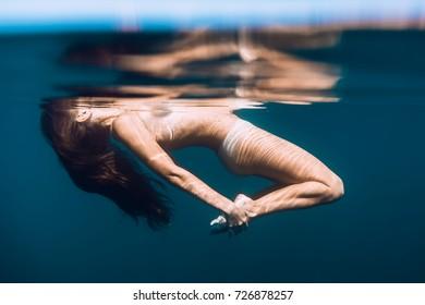 Slim woman relax in blue ocean, underwater photo