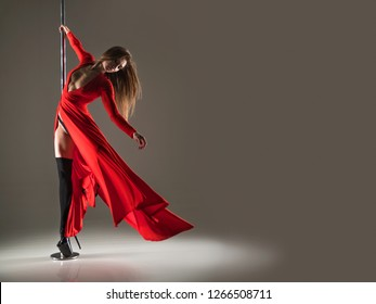 Slim woman in a sexy red dress and black stocking dancing on a pylon