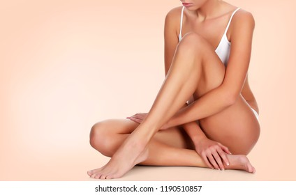 Slim woman touches her smooth skin on legs