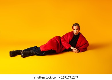 Slim woman in trendy outfit while lying on yellow background