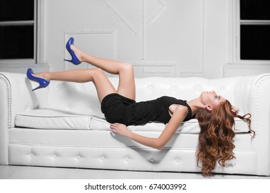 Slim woman wearing black dress and blue shoes posing on the white sofa