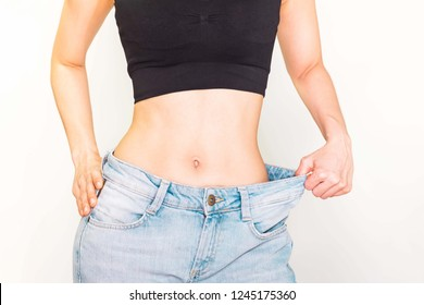 A slim woman wore jeans is showing how much weight she lost with a pink measuring tape around her waist.Selective focus