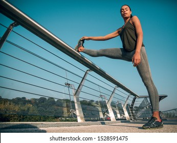 Slim young athlete putting foot on the banister and warming up muscles before the training