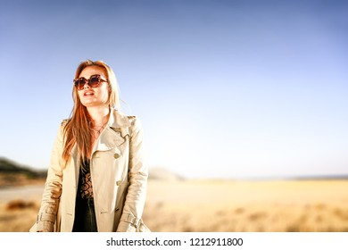 Slim young blond woman and autumn background of mountains and sea. Free space for your decoration.