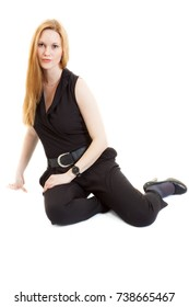 slim young blonde lass wearing a black overalls and sandals sitting, isolated on white