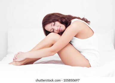 slim young brunette woman sleeping on the white linen in bed at home