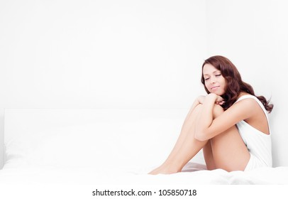 slim young brunette woman sleeping on the white linen in bed at home, copyspace for your text to the left