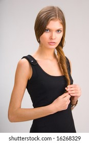 slim young girl in black holding her hair
