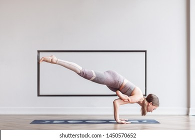 Slim young girl who loves acrobatics doing handstand. The concept of professional gymnasts and acrobats. Arm balancing handstand yoga asana, One Legged Crane Pose, Half Crow Pose, Eka Pada Bakasana
