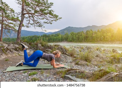 Slim young healthy sports girl doing the donkey kick exercise on all fours arching back straightening leg up concept sport, fitness, lifestyle. Work out and warm up outdoors in mountains near river.