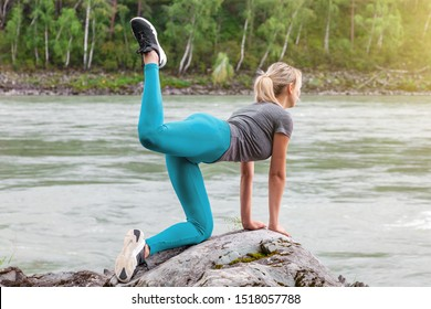 Slim young healthy woman doing the donkey kick exercise on all fours arching back straightening leg up. Concept sport, fitness, lifestyle. Work out and warm up outdoors in mountains near river.
