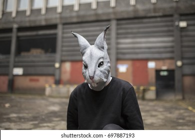 slim and young man wearing a rabbit mask and kneeling infront of some industrial buildings