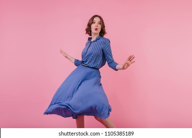 Slim young woman in blue midi skirt fooling around in studio. Graceful female model dancing with kissing face expression on pink background.