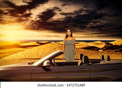 Slim young woman with car and landscape of sunset and ocean with beach. Summer time.