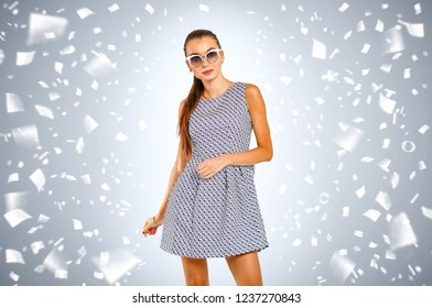 Slim young woman and cofetti decoration . Carnival time and gray background
