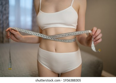 Slim young woman measuring her thin waist with a tape measure, close up.