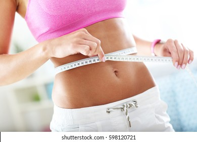 Slim young woman measuring her waist with a tape measure
