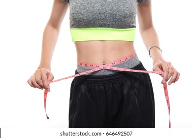 Slim young woman measuring her thin waist with a tape measure, charming tan skin Asian woman loss weight and show six pack waist muscle.