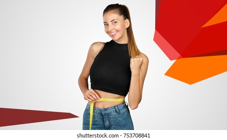 Slim young woman measuring her waist