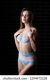 Slim young woman of model appearance posing in beautiful underwear on a black background. Girl love fashionable underwear and modern designer lingerie