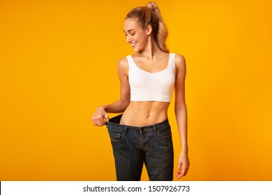 Slim Young Woman In Oversize Jeans Posing Over Yellow Background. Sport And Weight Loss. Studio Shot, Empty Space