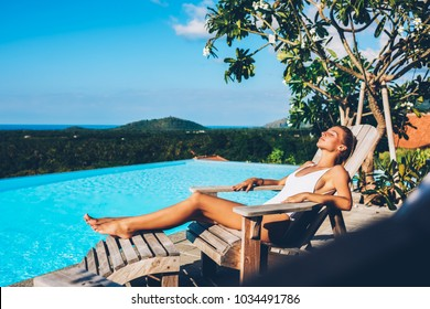 Slim young woman with sexy legs resting on wooden sun bed and sunbathing near blue swimming pool enjoying summertime. Female tourist in white swimsuit lying near basin during vacation in resort spa