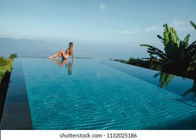 Slim young woman in swimsuit relaxing on edge tropical infinity pool in mountains. Palms around and crystal clean water. Luxury resort on Bali island