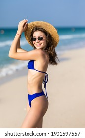 Slim young woman in trendy shades and hat poses on coastline against blue water being satisfied with good summer resort. Lovely fit female tourist on sandy beach alone