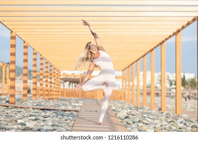 Slim young woman in a white gymnastic costume is standing on a wooden platform in the middle of a rocky beach and doing vrikshasana on a sunny summer day