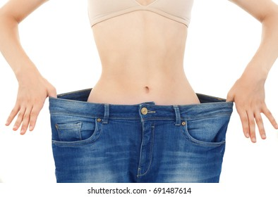 Slim Young Woman who Has Lost Weight Wears her Old Blue Jeans White Background.