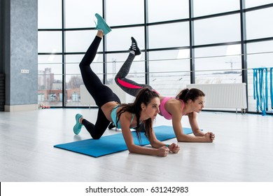 Slim young women doing bent knee donkey kick exercise in all fours position working out their buttocks in gym