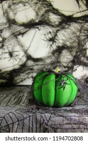 Slime Green Pumpkin with Spider Crawling up the side. Black Spiderwebs around the Halloween Design.