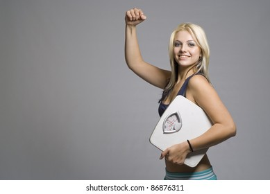 Slimming fit active woman happy with target weight scale and strong muscle bicep