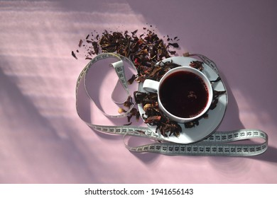 Slimming hibiscus tea.Sunlight through glass of window make light and shadow on pink background. Measuring tape and petals dried hibiscus in composition.Top view , copy space. Weight loss concept.