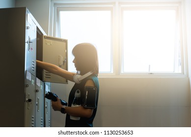 Slimmy Woman in locker room preparing for exercise with on-ear head phone and a pair of sport glove