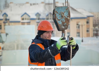 Sling fitter in a jacket and a helmet puts a cable on the hook