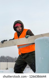 Sling fitter in a jacket and helmet unloads boards