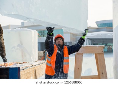 Sling fitter in a jacket and helmet unloads ice blocks