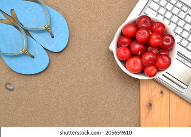Slippers, laptop and plums on wood and sand