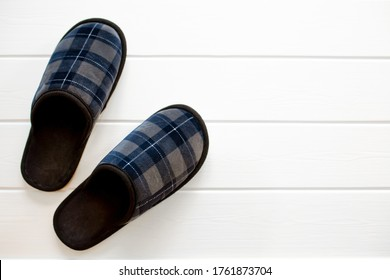 Slippers for men, on a white background of wooden parquet, home clothes. cute fluffy fur slippers home