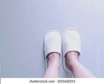 Slippers on women's legs. Soft comfortable home slipper. Female legs in slippers against the background of a wooden floor. Cozy, warm and comfortable slippers on the feet. Bed shoes accessory footwear