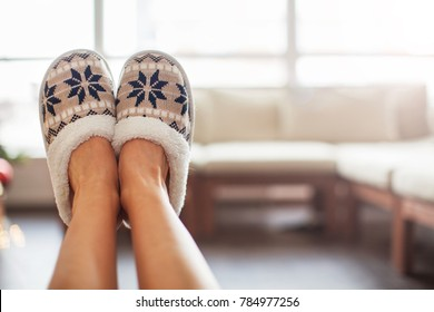 Slippers on women's legs. Soft comfortable home slipper