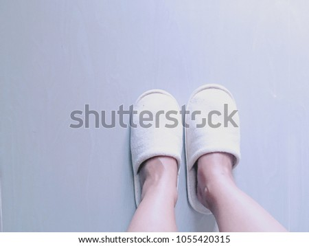 8a76a534a22f Soft comfortable home slipper. Female legs in slippers against the  background of a wooden floor. Cozy